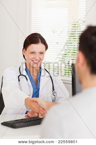A female doctor is shaking hands with a patient