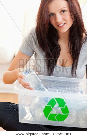 Woman recycling plastic bottles in a living room