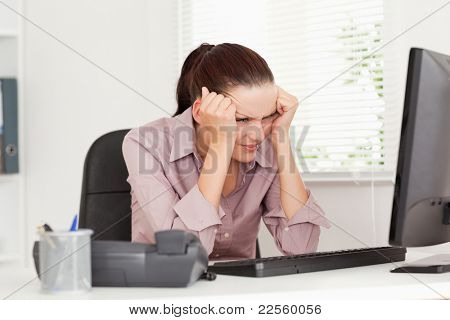 A frustrated businesswoman sitting in her office