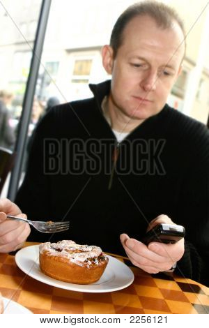 Man On Mobile Phone Having His Breakfast