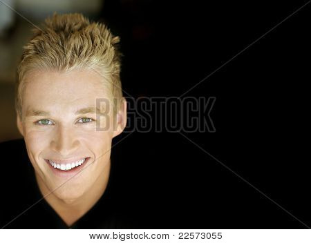 Close portrait of a sexy smiling male model against dark background with copy space