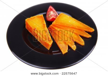 orange aged delicious cheddar cheese chop with slice and tomato on black plate isolated over white background