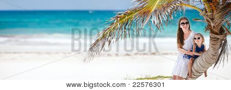 Panoramic photo of mother and daughter sitting on palm at Caribbean beach