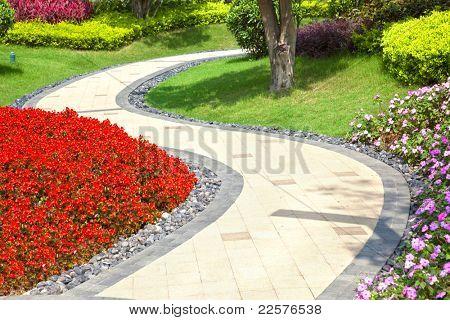 Schönen Sommergarten mit einem Gehweg windet sich durch