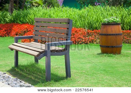 Beautiful summer garden with bench and big decorative wooden flowerpot