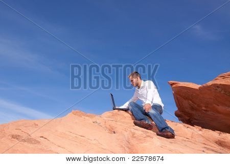 Young man outdoors with his laptop