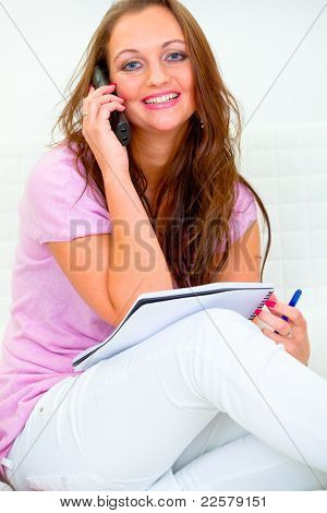 Happy Attractive Housewife Sitting On Sofa And Talking On Phone