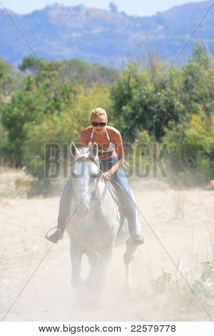 Young female riding her horse by the sea in Greece