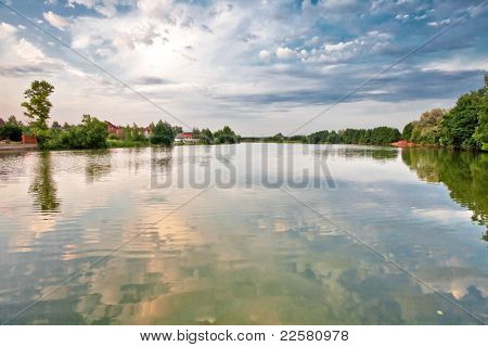 Green field with river under blue and sunset sky