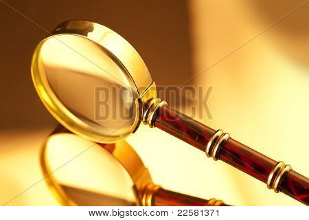 gold vintage magnifying glass on the mirror surface