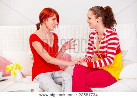 Two Pretty Girlfriends Sitting On Sofa And Talking