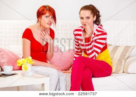 Two Surprised Girlfriends Sitting On Sofa