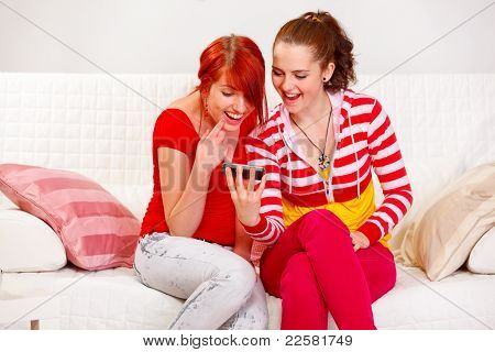 Happy Girl Showing Mobile To Her Smiling Girlfriend