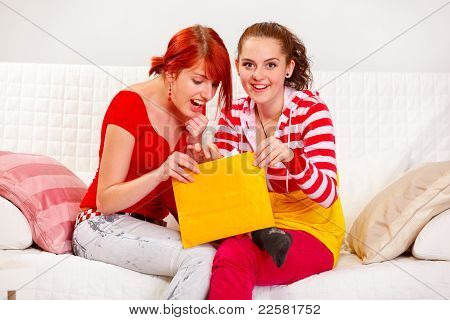 Cheerful Girlfriends Open Letter While Sitting On Sofa