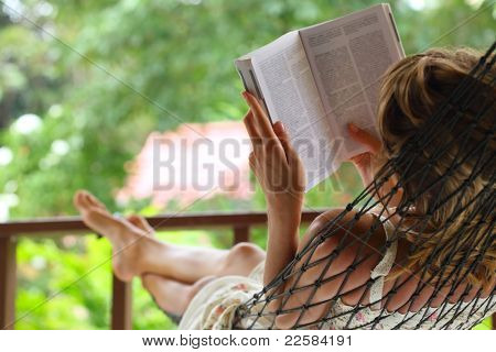 Young woman reading a book lying in hammock in a garden. Focus on the left hand and shoulder