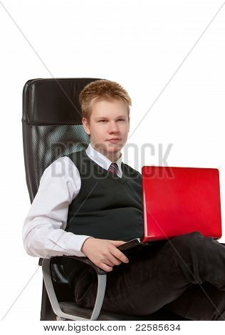 The happy schoolboy in office armchair with the laptop