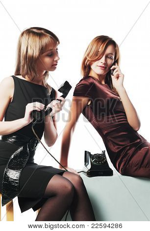 Two young women with a retro and modern phones