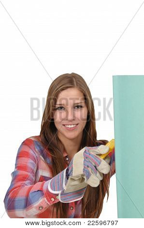 Young woman cutting green board drywall