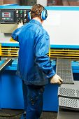 pic of guillotine  - worker at workshop operating guillotine shears machine - JPG