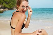 Adorable Young Female Has Fun At Seashore, Glad To Pose At Camera, Looks Through Sunglasses With Joy poster