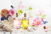 Bottles with essential aroma oil,towels different colors and fresh flowers  on white wooden backgrou poster