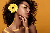 Young Sensual African American Woman With Artistic Make-up And Gerbera In Hair Tenderly Touches Her  poster