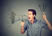Side Portrait Angry Young Man Holding Screaming In Megaphone Isolated On Gray Background. Negative F poster