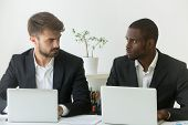 Multiracial Office Rivals Looking At Each Other With Hate Envy Sitting With Laptops, Corporate Compe poster