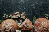 Homemade Loaf Of Irish Soda Bread With Eucalyptus Leaves And Little White Flowers On Black Stone poster