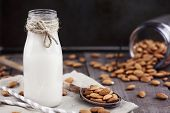 Organic White Almond Milk In A Glass Bottle With Whole Almonds Spilled Over A Rustic Wooden Table. poster