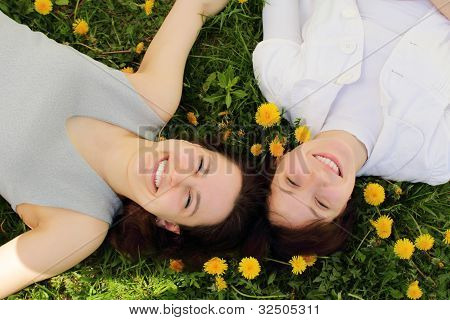 Two Beautiful Young Girls Lie Side By Side On The Grass
