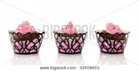 Three chocolate cupcakes with pink butter cream isolated over white background