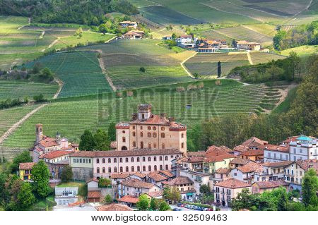 Aerial view on small town and Barolo castle among hills and vineyards of Piedmont, Northern Italy.