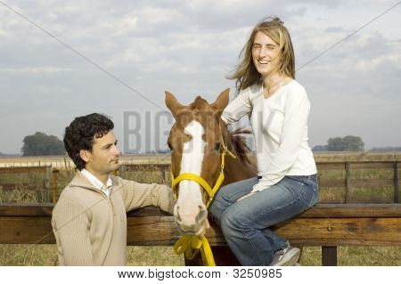 Young Couple Relaxing With Their Horse