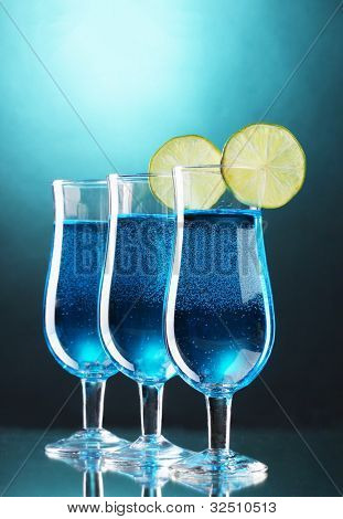 Blue cocktail in glasses with lime on blue background