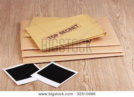 Envelopes with top secret stamp with photo papers on wooden background