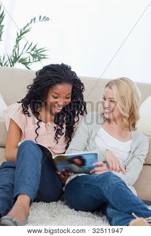A surprised looking woman is reading a magazine with her friend