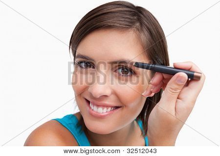 Young attractive woman using an eyebrow pencil to make-up