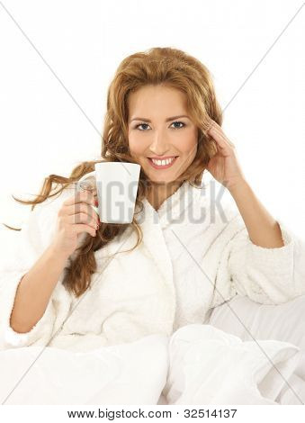 Young attractive woman in towel drinks coffee