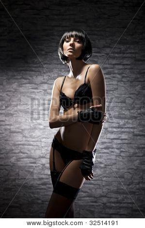 Fashion shoot of young bizarre woman in fetish dress