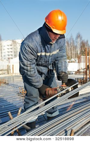 Authentic worker builder with grinding machine cutting reinforcement rods elements for concrete pouring at construction building area site
