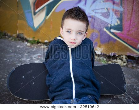 Young Boy With Skateboard Against A Graffiti Wall