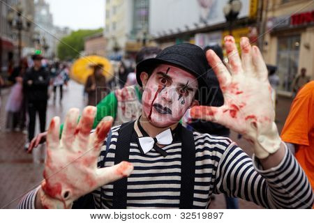 MOSCOW - MAY 14: Unidentified made-up participant - clown-murderer in a striped shirt with bow-tie, in bowler and gloves - at Zombie Parade on Old Arbat, May 14, 2011, Moscow, Russia.