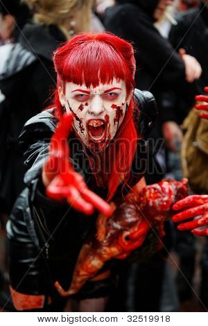 MOSCOW - MAY 14: Unidentified red-haired screaming made-up female participant with bloody face and with dead bloody baby-doll in her arms at Zombie Walk on Old Arbat, May 14, 2011, Moscow, Russia.