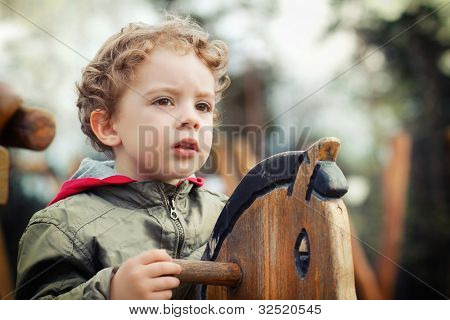 cute little boy playing on the playground outdoor