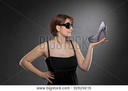 brunette woman with sunglasses holding shoe