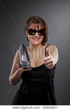 woman with shoe posing thumbs up