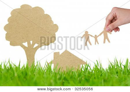 Paper cut of house and tree on fresh spring green grass
