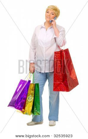 Senior woman with bags and mobile phone isolated