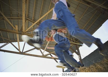 Low angle view of children jumping in hay